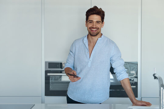 Man resting in kitchen and using smartphone
