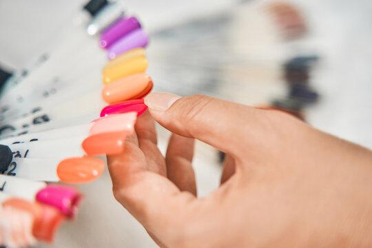 Female person pointing at bright nail polish