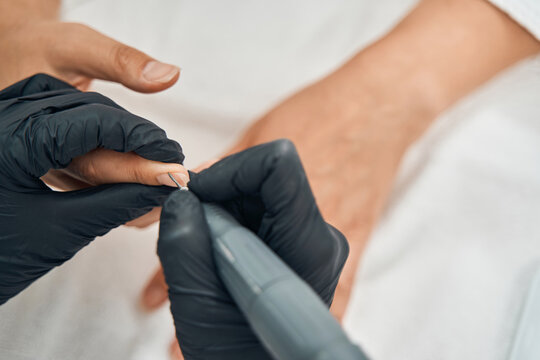 Competent nail master removing cuticle with device