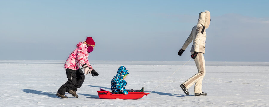 Young adult mother wear warm jacket enjoy have fun sledging two cute little sibling kids boy girl at frozen white snow lake field against clean blue sky landscape bright sunny cold winter day. Outdoor