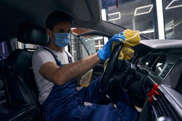 Caucasian auto repair mechanic wiping automobile driving wheel