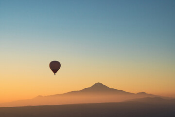 hot air balloon silhouette with a high Erciyes mountain peak in the background