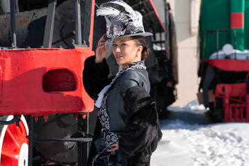 girl dressed as a noblewoman of the 19th century near a steam locomotive. Russian winter