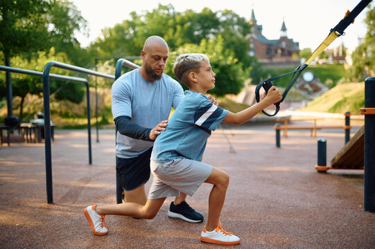 Father and son, exercise with ropes on playground