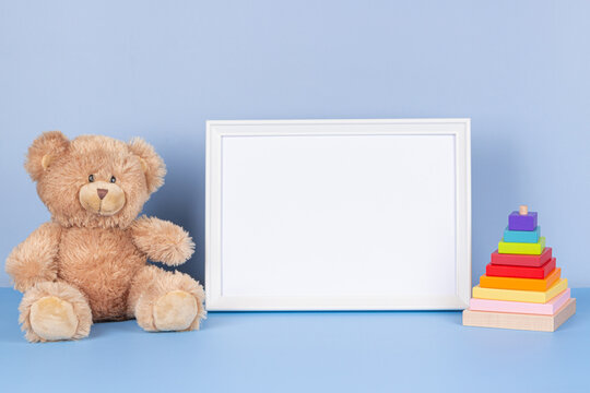 White wooden picture frame with blank mock up copy space standing next to teddy bear and colorful wooden toy pyramid on light blue background. Front view