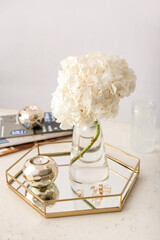 Obraz Beautiful hydrangea in glass vase and stylish decor on table in interior of light room - fototapety do salonu