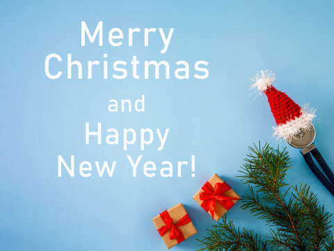 inscription Merry Christmas and Happy New Year medical banner, gift boxes, stethoscope in Santa hat and Christmas tree on blue background. Close-up. Top view, flatlay, greeting card
