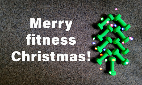 Merry fitness Chrismas wallpaper with creative Christmas Tree made of green dumbbells and bokeh. Flat lay, top view minimalistic background, Gym Fitness greeting card
