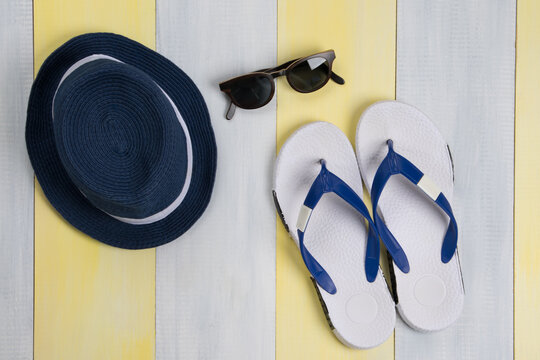 on a gray-yellow surface, beach flip-flops, sunglasses and a hat