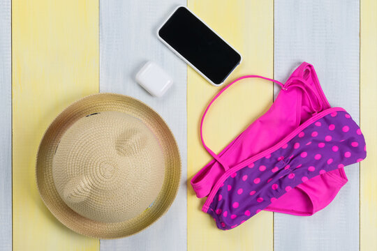 on a gray-yellow surface, a children's swimsuit, a hat and mobile gadgets, a phone and wireless headphones in a case