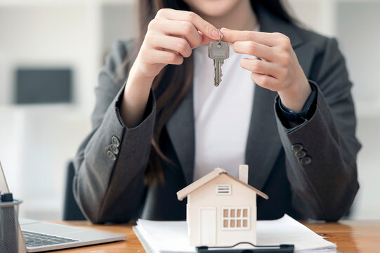 woman hand holding key, real estate concept.