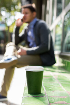 Man walking on the street, drinking coffee, talking by phone