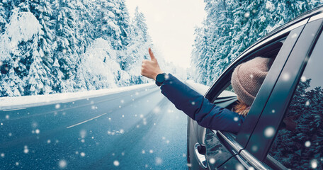 Obraz Happy woman in the car gesture finger up on the snowy background. - fototapety do salonu