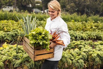 Obraz Smiling young chef carrying fresh vegetables on a farm - fototapety do salonu