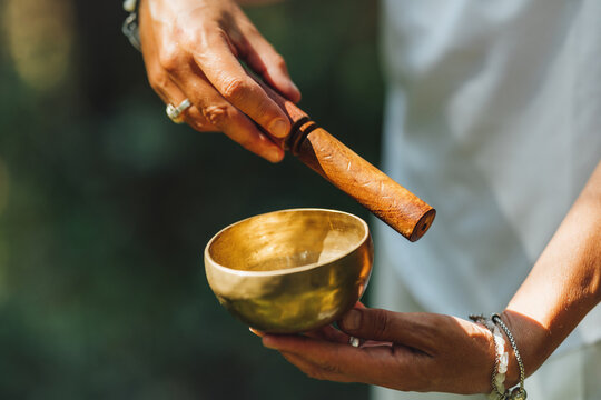 Hands of a Woman Playing Tibetan Singing Bowl in Nature