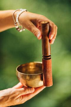 Hands Holding Tibetan Singing Bowl Outdoors