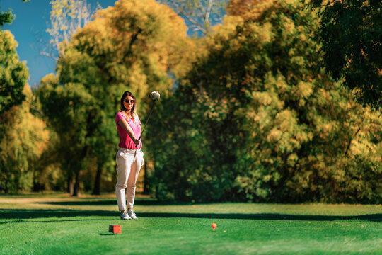 Beautiful female golfer getting ready on the tee box