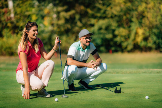 Golfing lifestyle. Golf couple on the putting green, enjoing the beautiful sunny day