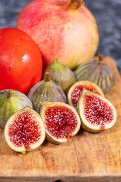 Wooden board with figs and other autumn fruits.