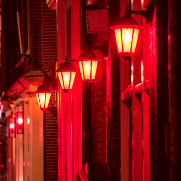 Background - Red light district in Amsterdam at night.  Selective focus on one lamp and defocus the rest. Amsterdam, Holland, Europe
