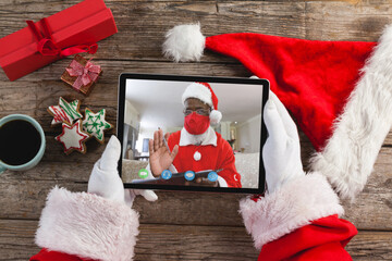 Fototapeta premium Hands of santa claus holding tablet with santa claus in face mask on screen