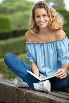 woman wearing off-the-shoulder top sat cross legged on bench reading