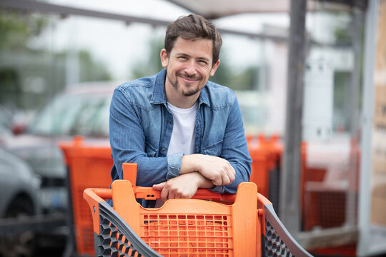 man with a shopping cart on a parking lot