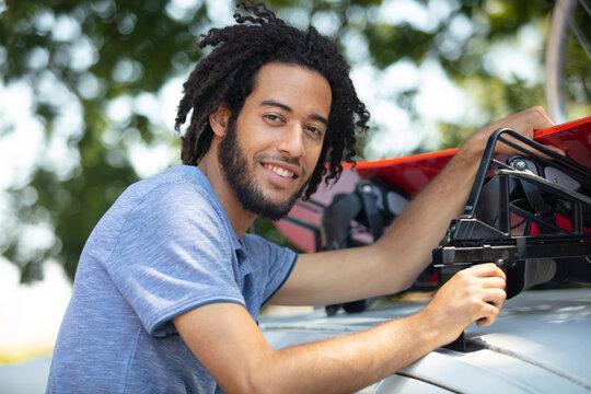 happy man fixing a car roof