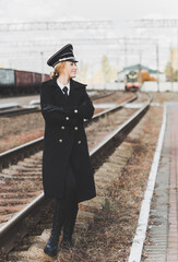 European or American train conductor is on his duty on a platform and other trains. Railway, steam trains .Train controller on the train, near a locomotive