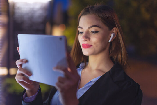 Young businesswoman reading messages on tablet at evening