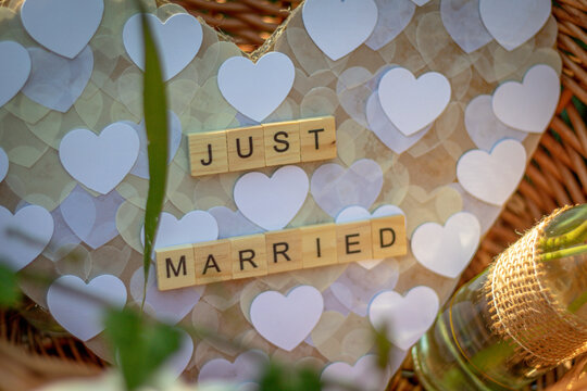 a heart with the words Just married made of single wooden letters in a basket as decoration at wedding celebration