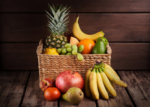 Mix of fresh juicy colorful exotic tropical fruits in basket on wooden background