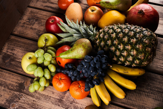 Mix of fresh juicy colorful exotic tropical fruits on wooden background top view