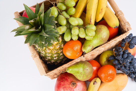 Mix variety of fresh juicy colorful exotic tropical fruits in basket on white background top view