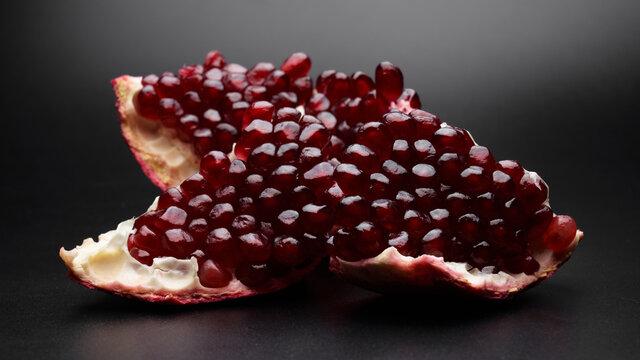 Red ripe fresh juicy sliced pomegranate isolated on black background