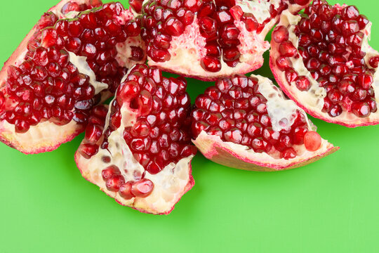 Red ripe fresh juicy sliced pomegranate isolated on green background