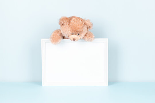 Cute toy teddy bear on white wooden picture frame with blank mock up copy space, light blue background. Front view