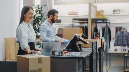 Clothing Store Checkout Cashier Counter: Female and Male Retail Sales Managers Carefully Packing Online Ordered Clothes into Boxes. Fashionable Shop, with Stylish Brand Designs Available on Internet