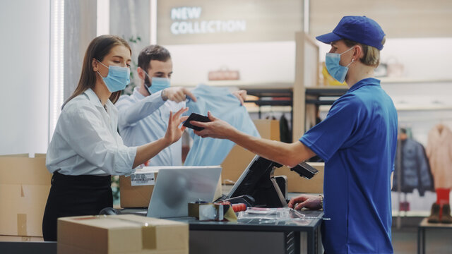 Clothing Store Checkout Cashier Counter: Female and Male Retail Sales Managers wearing Protective Face Masks Give Package to Online Order Delivery Person. Designer Brands Available on Internet