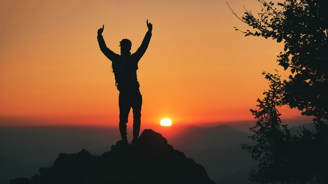 Man in silhouette in front of idyllic sunset in the hills