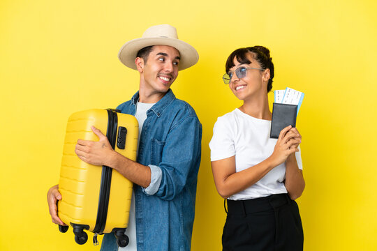 Young traveler friends holding a suitcase and passport isolated on yellow background looking over the shoulder with a smile