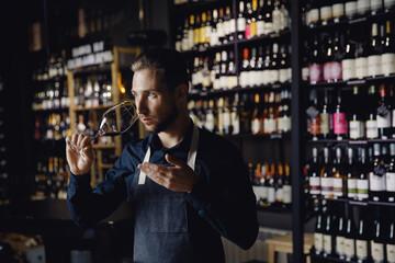 Fototapeta Winemaker sommelier man sniffing aroma red wine in glass background bottles restoran obraz
