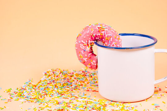 Strawberry donut with colored sprinkles in a cup.