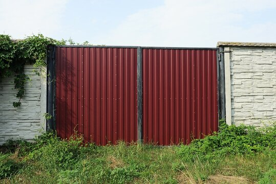 one closed red metal gate and a white wall of a concrete fence with green vegetation and grass on the street
