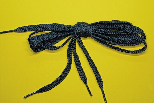 skein of blue fabric laces on a yellow table