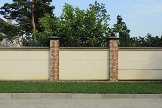 a long wall of a fence made of gray concrete and brown bricks outside in green grass