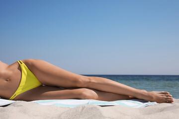 Obraz Woman in bikini lying on sandy beach near sea, closeup - fototapety do salonu