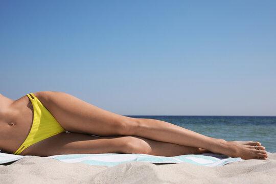 Woman in bikini lying on sandy beach near sea, closeup