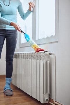 Woman with a dust stick cleaning central heating gas radiator at home.