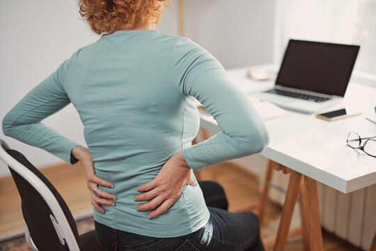 Woman with hip, back, spine spasm, cramp and pain, working from home troubles and issues.